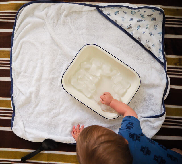 Baby Play Idea, baby playing with ice cubes on towel
